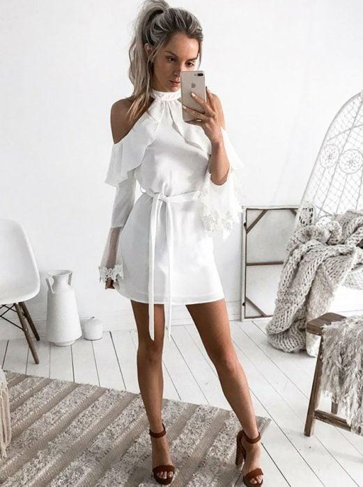 Chica usando un vestido de color blanco corto con mangas de olanes