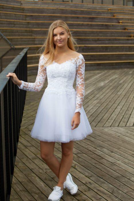 Chica usando un vestido blanco de encaje con tul en la falda