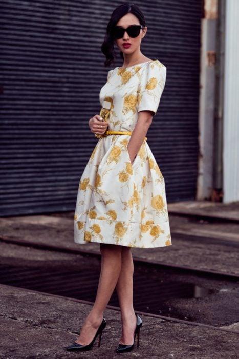 Ideas de vestidos para boda en jardín al aire libre; mujer con vestido blanco, con flores amarillas, cinto amarillo delgado y tacones stiletto