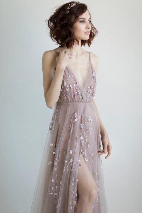 Ideas de vestidos para boda en jardín al aire libre; mujer con cabello castaño corto y ondulado, con corona de flores, con vestido de tul color beige, con flores tejidas, de tirantes y abertura en la pierna