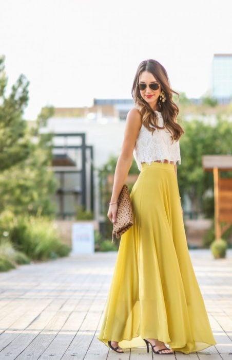 Ideas de vestidos para boda en jardín al aire libre; chica con falda larga y amarilla, top blanco con encaje, sandalias de tacón y bolsa de mano de animal print