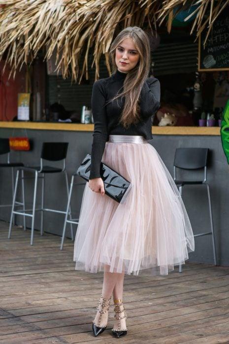Ideas de vestidos para boda en jardín al aire libre; chica de cabello largo y suelto, con blusa negra, de cuello alto y mangas, con falda rosa de tul, bolsa negra de mano y tacones con estoperoles