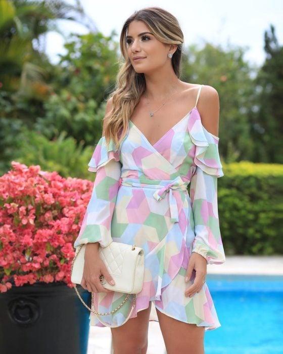 Ideas de vestidos para boda en jardín al aire libre; chica de cabello rubio estilo balayage, con jumpsuit corto, de tirantes, con figuras geométricas de colores rosa, amarillo, verde y azul