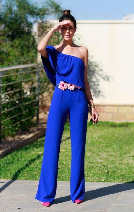 Ideas de vestidos para boda en jardín al aire libre; mujer de cabello castaño con peinado de chongo alto, tapándose el sol con la mano, usando jumpsuit azul rey largo, con cinturón de flores