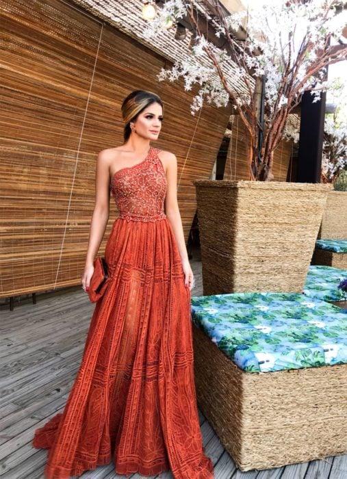 Ideas de vestidos para boda en jardín al aire libre; mujer con vestido largo de un solo hombro, color terracota, con encaje