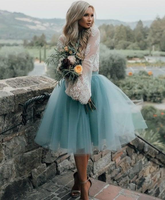 Ideas de vestidos para boda en jardín al aire libre; chica de cabello rubio platinado, largo y ondulado, con falsa de tul estilo bailarina de color azul, y top de encaje blanco, posando con un ramo de flores