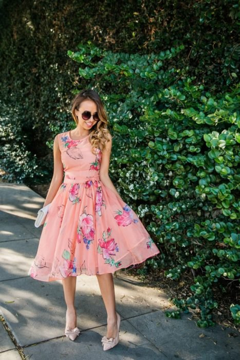 Ideas de vestidos para boda en jardín al aire libre; chica junto a una enredadera con vestido de tul rosa con flores, stilettos con moños y lentes de sol redondos