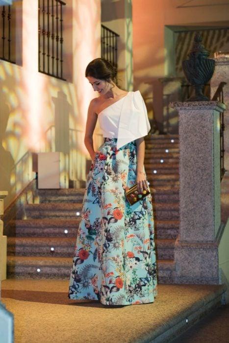 Ideas de vestidos para boda en jardín al aire libre; chica con vestido de fiesta, falda azul floreada, top blanco de un solo hombro y bolsa de mano