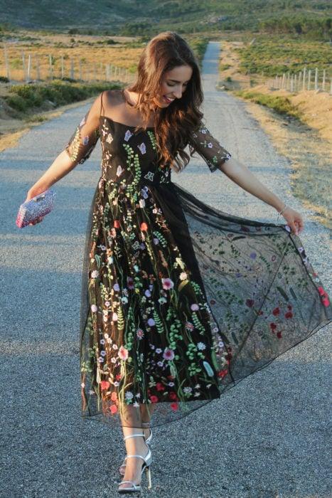 Ideas de vestidos para boda en jardín al aire libre; chica caminando en la carretera feliz, con vestido negro de encaje con flores y sandalias de tacón delgado, bolsa de mano con glitter