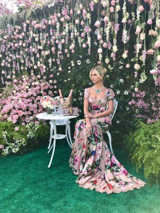 Ideas de vestidos para boda en jardín al aire libre; chica rubia con cabello agarrado en chongo, con vestido rosa floreado, largo hasta el suelo, sentada en un jardín con rosas blancas y rosadas