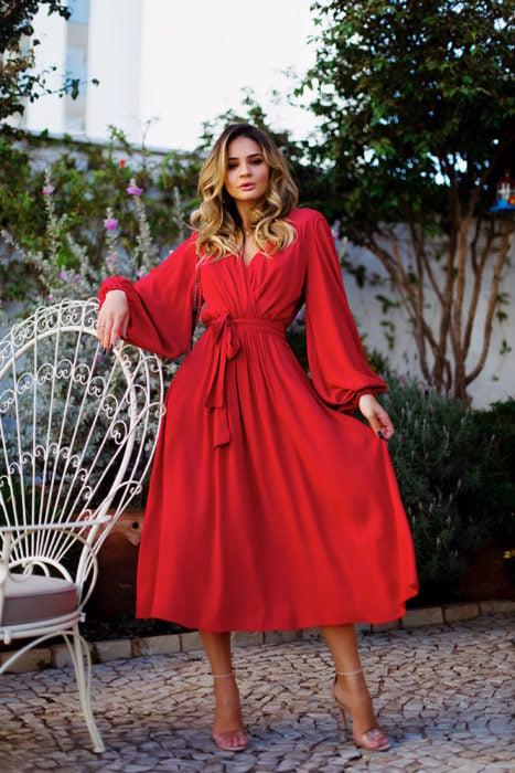 Ideas de vestidos para boda en jardín al aire libre; mujer con vestido rojo de escote cruzado, con listón en la cintura y mangas
