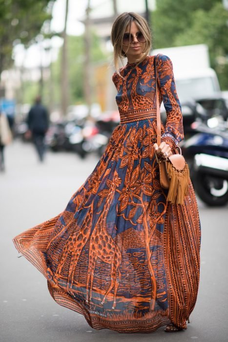 Ideas de vestidos para boda en jardín al aire libre; mujer rubia con peinado despeinado, lentes de sol grandes y redondos, con vestido azul y anarangado, con mangas y largo hasta el suelo, con estampado de árboles y jirafas