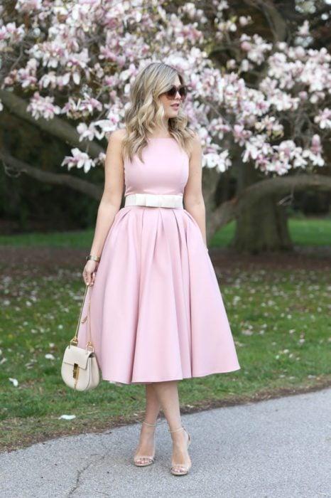 Ideas de vestidos para boda en jardín al aire libre; chica de cabello rubio y ondulado, con lentes de sol, vestido rosa, cinturó blanco, stilettos abiertos y bolsa color hueso, posando frente a un árbol de flores rosas