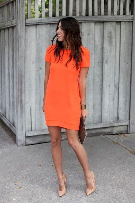 Ideas de vestidos para boda en jardín al aire libre; chica de cabello castaño y ondulado, con vestido sencillo anaranjado, de manga corta y liso, con tacones color beige y bolsa de mano