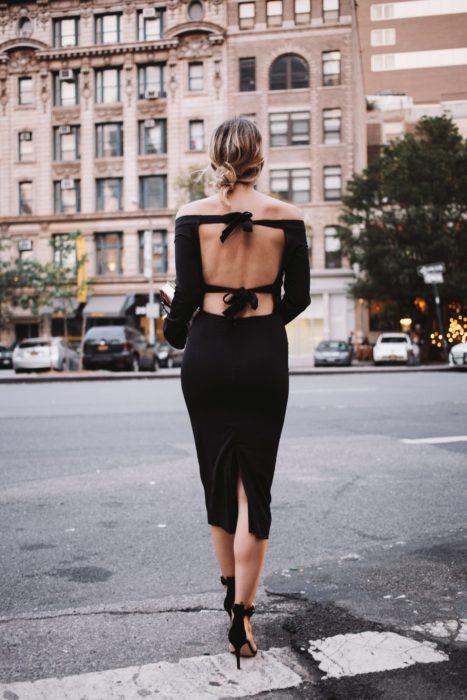 Chica usando un vestido de color negro con tacones de pulsera