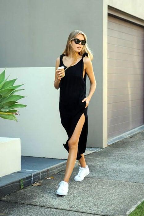 Chica usando un vestido largo con abertura en una pierna y tenis blancos