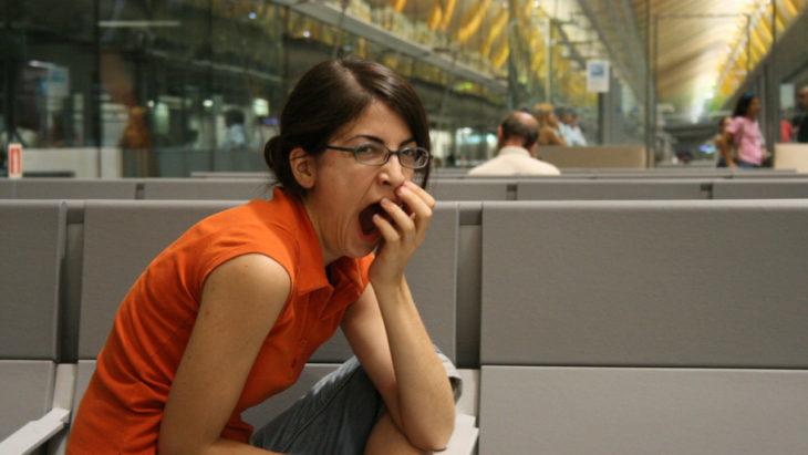 mujer bosteza mientras trabaja