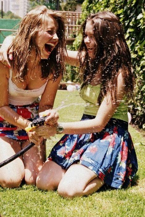 dos mujeres jóvenes riendo mientras se mojan con agua
