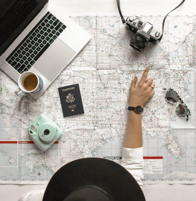 Mujer señalando una ruta en un mapa que esta desplegado y detenido por una cámara digital, una lap top y su pasaporte