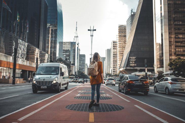 Chica a mitad de avenida admirando los edificios a su alrededor mientras modela para fotografía