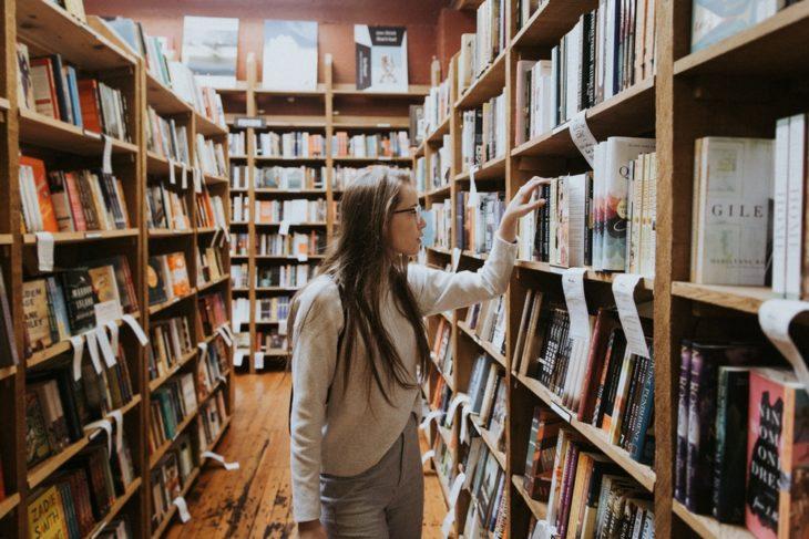 Chica dentro de un pasillo de biblioteca buscando un libro