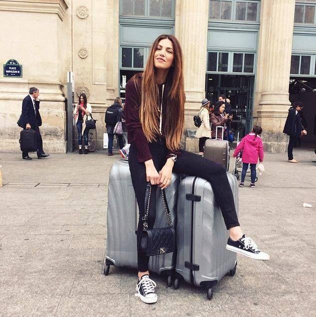 Chica desalineada sentada sobre sus maletas, posando para una fotografía frente a un edificio