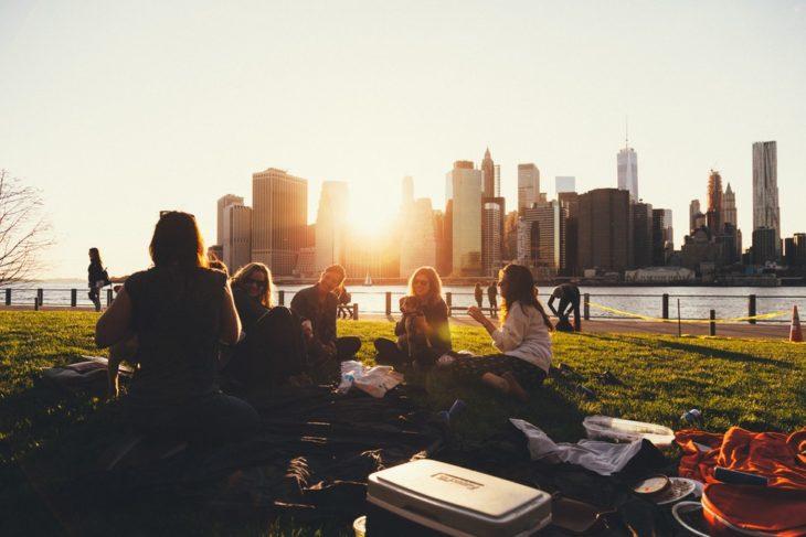 Grupo de jóvenes sentados en en el pasto frente a un lago, mientras estudian y charlan