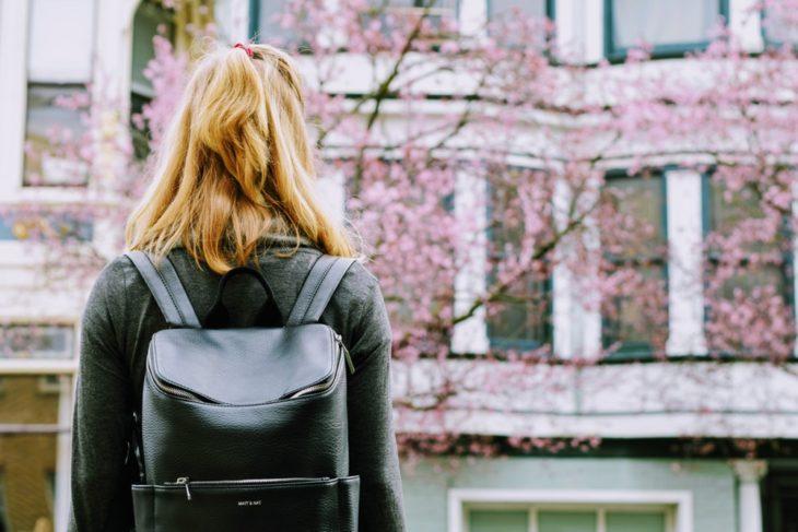 Chica girada de espaldas vestida de negro admirando en árbol con petalos rosas