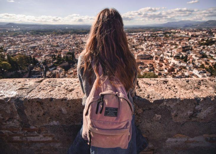 chica de espaldas mostrando su mochila de color rosa y admirando en paisaje cubierto de casas y edificios antiguos