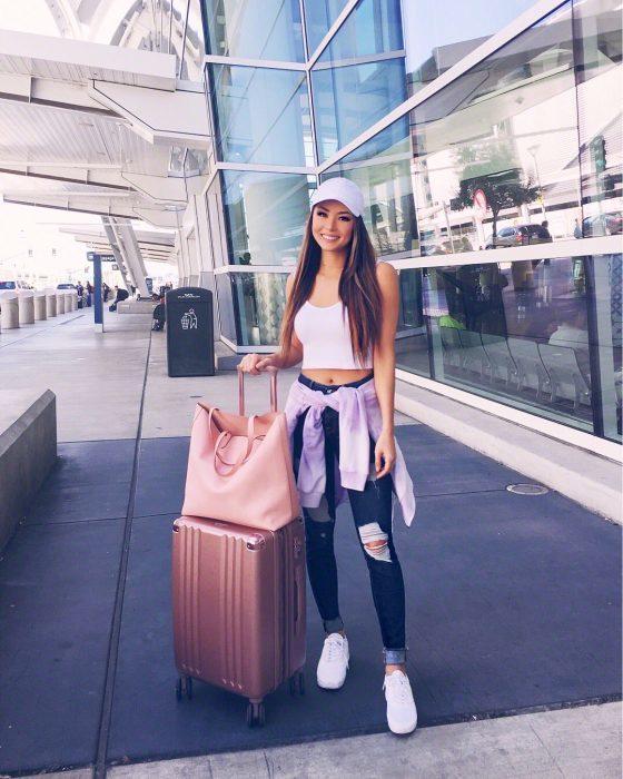 Chica sosteniendo su maleta color rosa fuera del aeropuerto, despidiéndose antes de abordar su vuelo