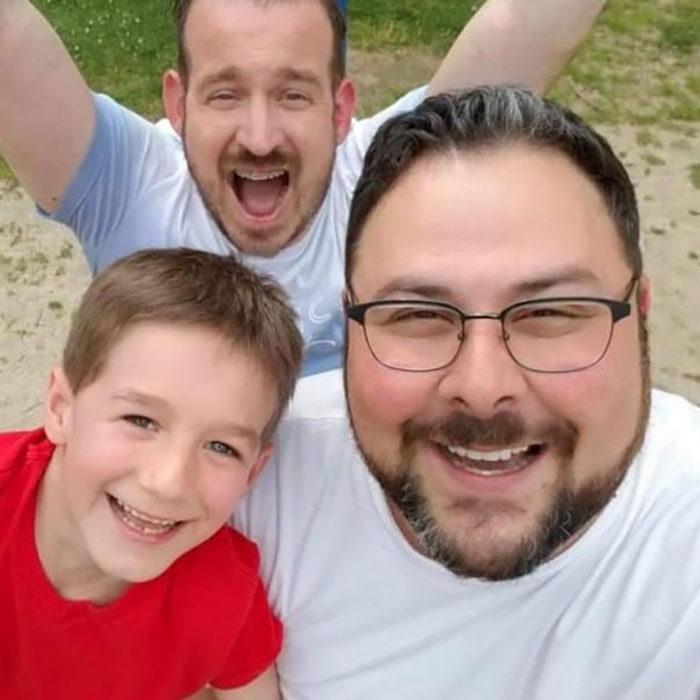 Paul y Gregg padres que adoptaron a un niño, posando para una selfie en la que sonríen