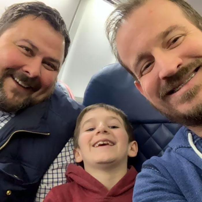 paul y gregg padres que adoptaron a un niño, posando con el pequeño durante un viaje en avión