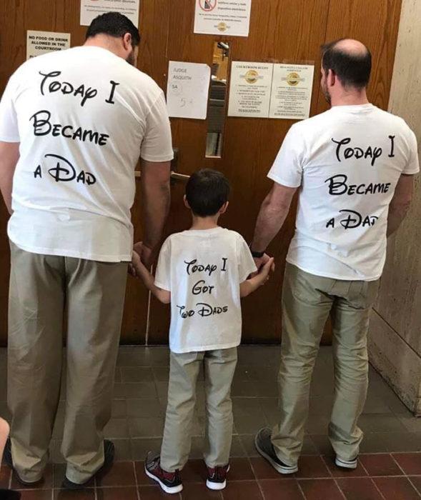 """Paul y Gregg pareja que adoptó a un niño, celebrando la adopción con camisas del rey león que dicen """"hoy me convertí en papá"""""""