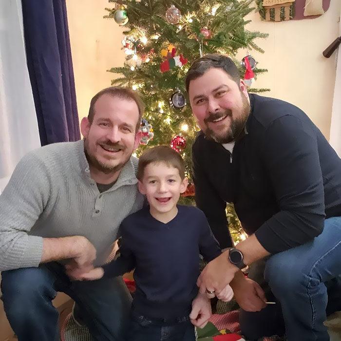 Paul y Gregg padres que adoptaron a un niño, posando para una selfie en la que sonríen mientras celebran la Navidad