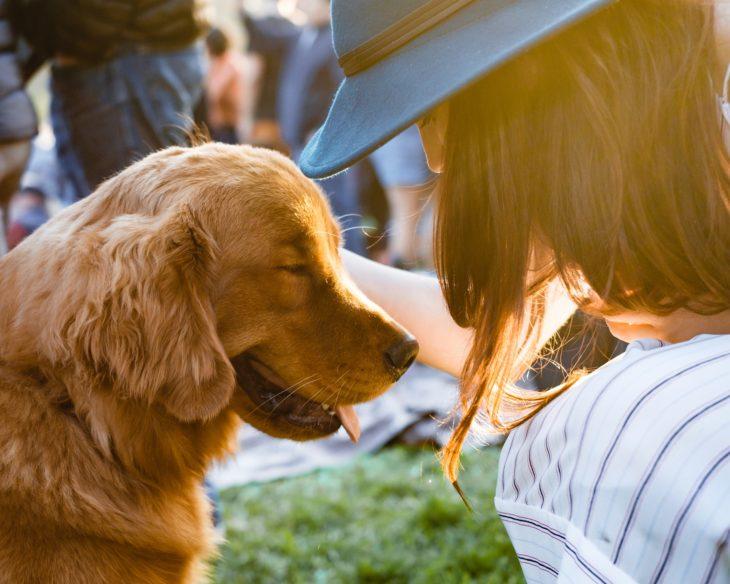 mujer con perro dorado