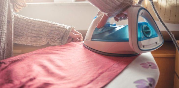 una mujer está planchando una prenda color melón