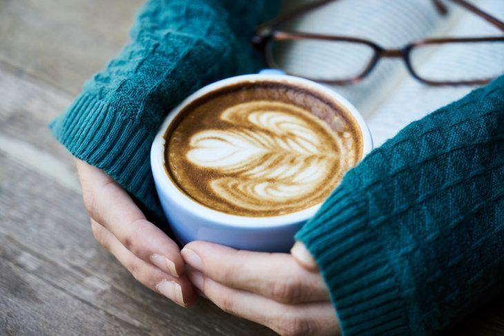 unas manos de mujer con un suéter azul abrazan una taza de café