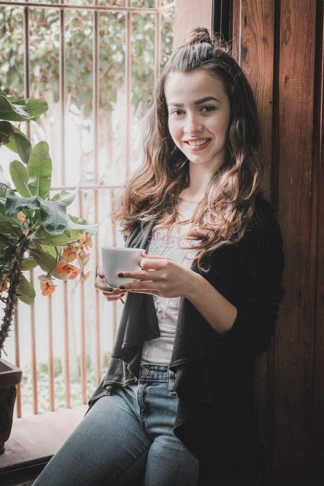 una mujer recargada en una ventana toma una taza de café con las dos manos