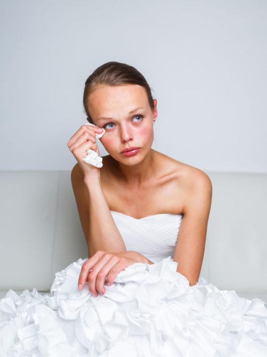 una joven vestida de novia sentada se limpia una lágrima con un pañuelo desechable