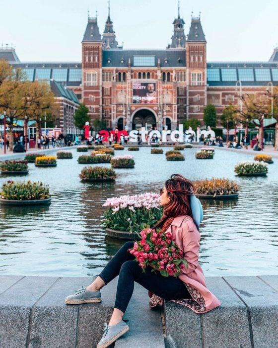 Chica con ramo de flores frente a río Amstel en Ámsterdam