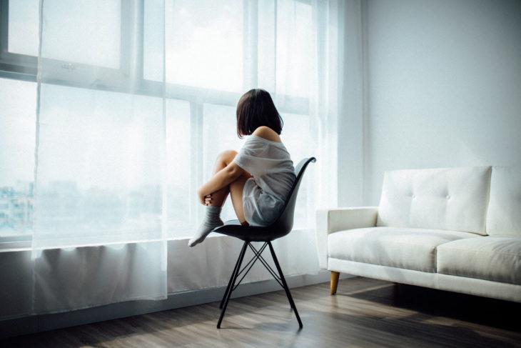 chica sentada en una silla en medio de una habitación