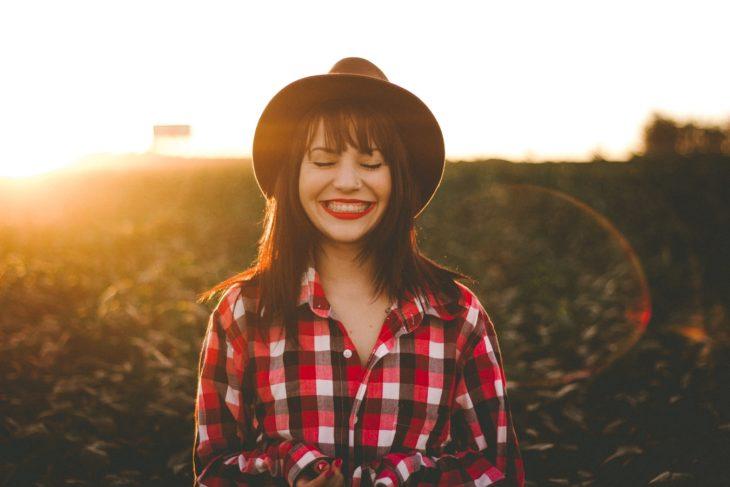 chica con sombrero sonriendo en el campo