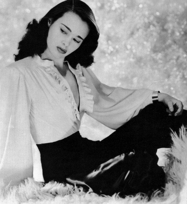 Gloria Vanderbilt posa en su juventud con una blusa blanca de olanes abierta y una falda negra