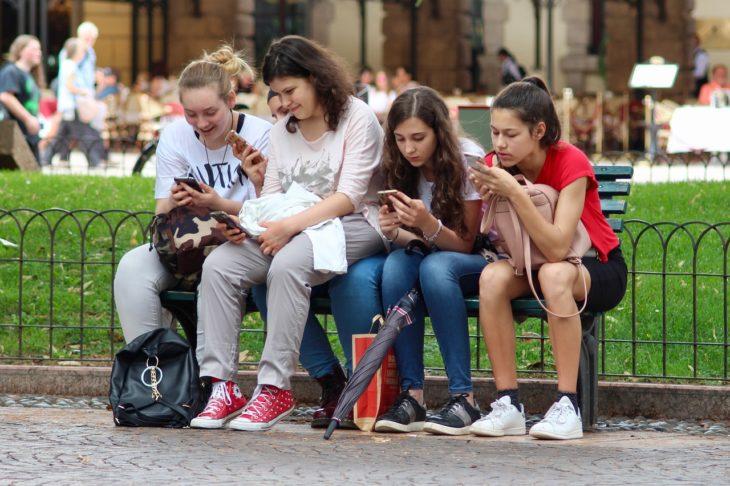 cuatro jovencitas viendo sus celulares sentadas en un jardín