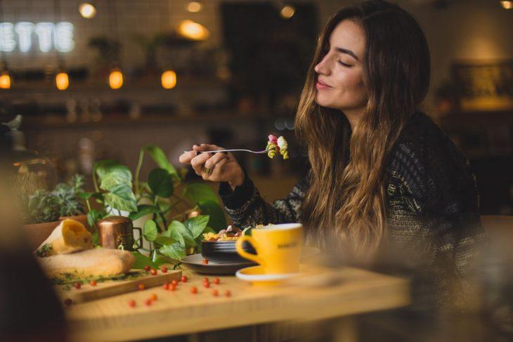 mujer cabello largo sentada en la mesa comiendo ensalada