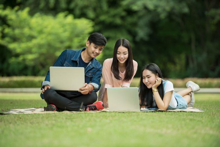 tres jóvenes sentados en el césped ven dos computadoras portátiles