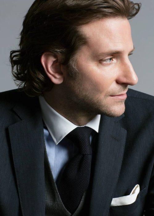 Actor, director y cantante Bradley Cooper de perfil, con traje y corbata