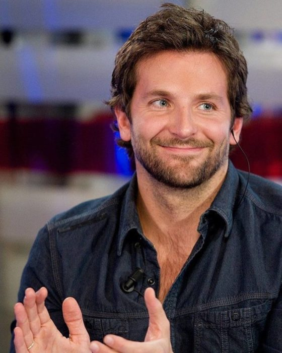 Actor, director y cantante Bradley Cooper sonriendo con una camisa de mezclilla