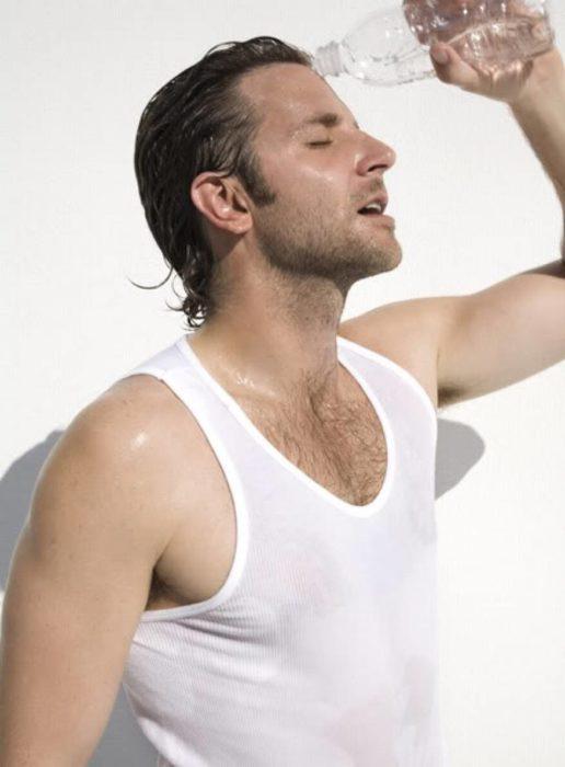 Actor, director y cantante Bradley Cooper mojándose con una botella de agua