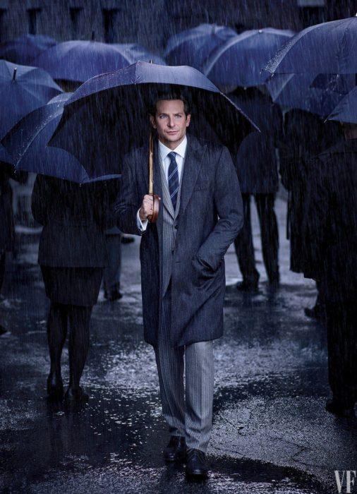 Actor, director y cantante Bradley Cooper en sesión de fotos para Vanity Fair, caminando con traje y paraguas bajo la lluvia